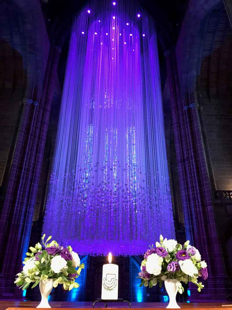 Full image of shafts of purple light, floral decoration and lit candle.Road Peace – Remembrance of Diana, Princess of Wales and All Road Crash Victims, Tuesday 31st August 2021 at Liverpool Cathedral